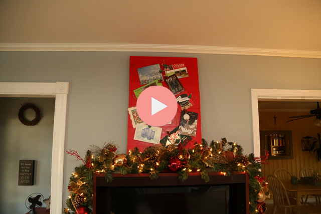 christmas card holder sitting on top of entertainment center in room with blue walls