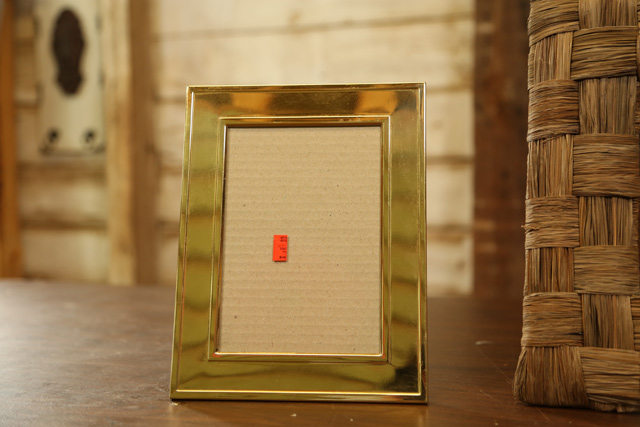 gold brass picture frame on table with orange price sticker