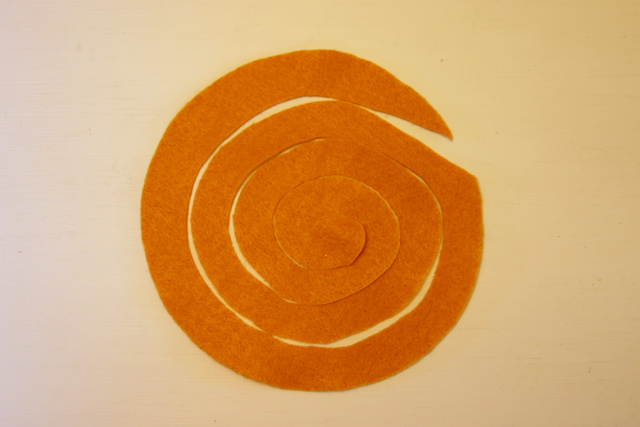 orange felt cut in spiral on white table