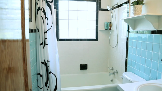White bathroom tub with window and blue tile walls.