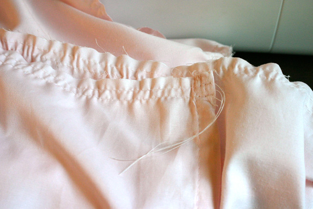 two long basting stitches on pink fabric to create ruffle