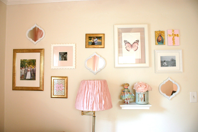 pink white and gold frames hanging in gallery wall in nursery