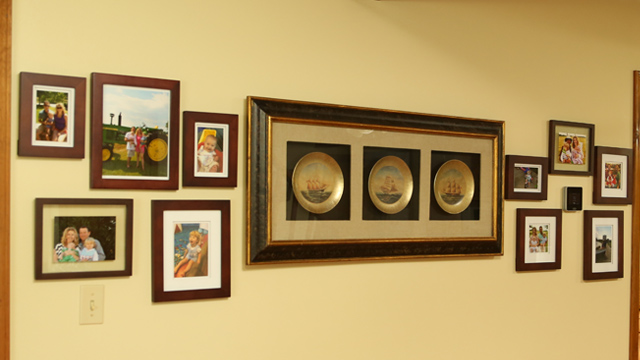 wood stained photo frames in gallery wall with carrier cor thermostat