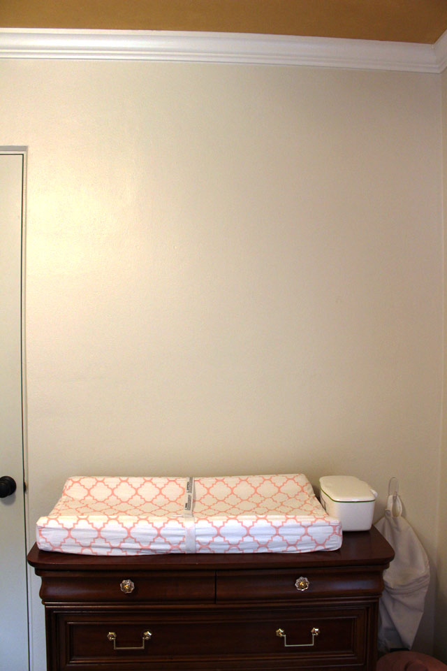 empty white nursery wall above pink changing table pad