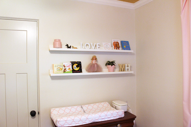 decorated picture ledges hanging on wall above changing  pad on cherry dresser