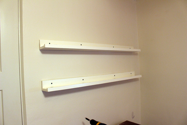white picture ledges hung on wall with blue screws