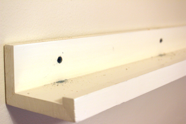 blue tapcon screws sunken in back of white wood picture ledge