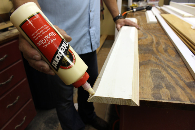 applying Titebond wood glue to indoor shelf board