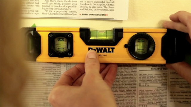 using torpedo small level to check nails for picture frame