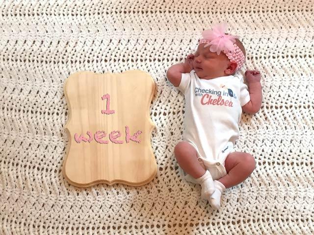 newborn baby girl with 1 week wooden plaque