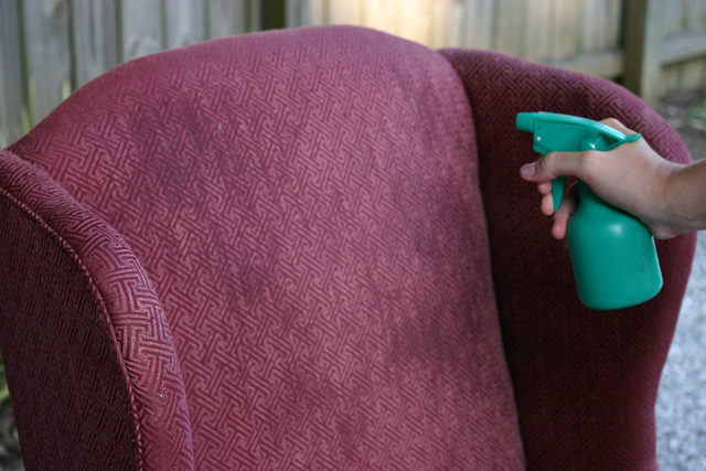 spray bottle misting fabric on armchair before painting