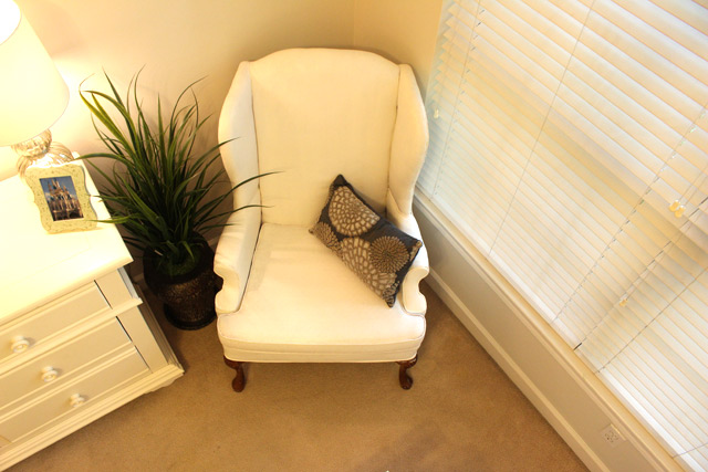 armchair in corner of bedroom with fake green plant and pillow