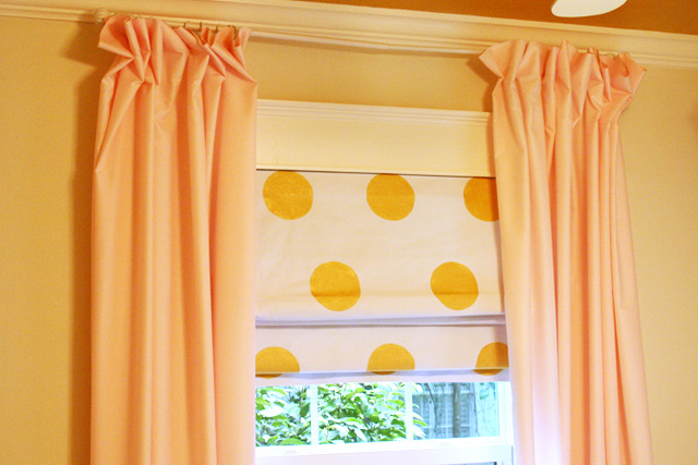 gold polka dot roman shade with pink curtains in white window