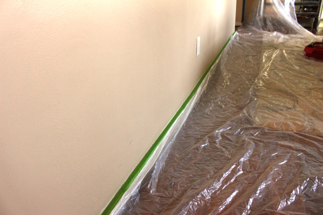 green painter's tape holding plastic in place along baseboard