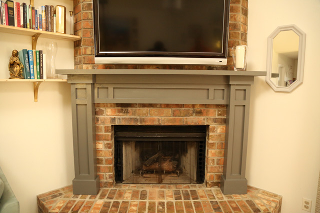 wood fireplace mantel with legs over brick fireplace and hearth