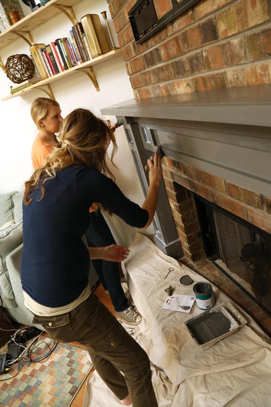 2 females painting gray fireplace mantel