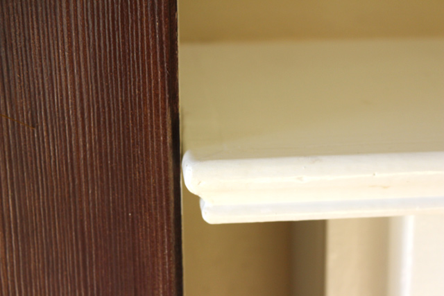 dark stained fiberglass door hitting side of fireplace mantel