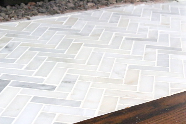 gray and white herringbone marble tile fireplace hearth