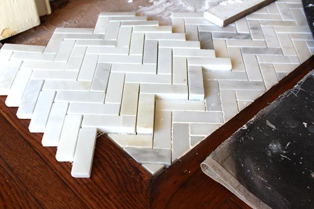 white and gray herringbone tile mat on top of already laid tile near hardwood floors