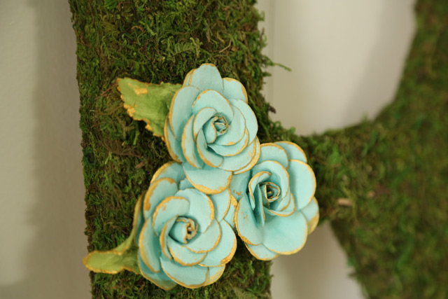 blue paper flowers on moss-covered initial