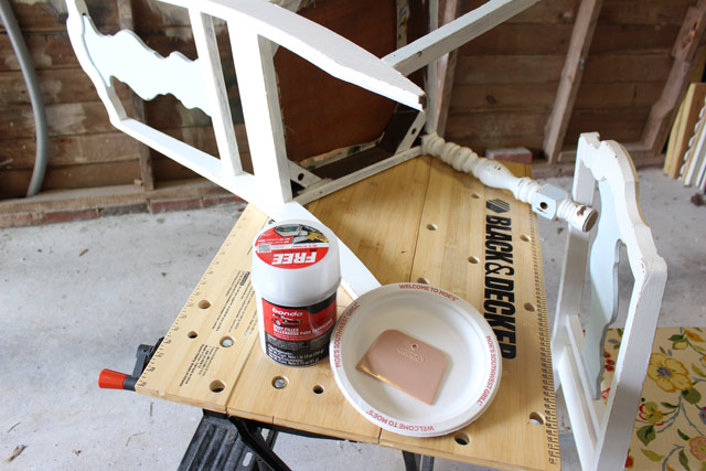 can of bondo sitting on workbench repairing wooden chair leg