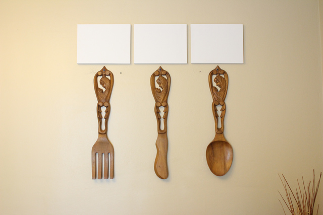 Giant Wooden Fork Knife Spoon Hanging On Yellow Wall With White Canvases Above Them