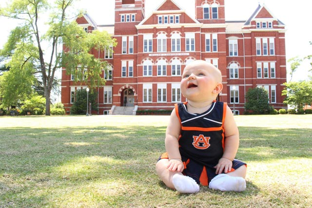7 month old baby in Auburn cheerleading uniform in front of Samford Hall