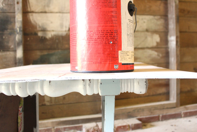paint can sitting on top of plywood on top of wooden chair