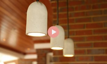 concrete pendant lights hanging over bar in brick outdoor kitchen