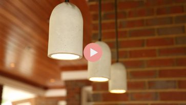 concrete pendant lights hanging over bar in brick outdoor kitchen