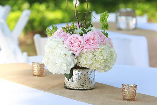 burlap table runner on white tablecloth pink roses and white hydrangea wedding reception table setting garden party