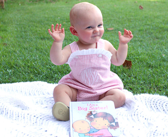 9 month old baby girl pose pink bubble outfit big sister book white blanket