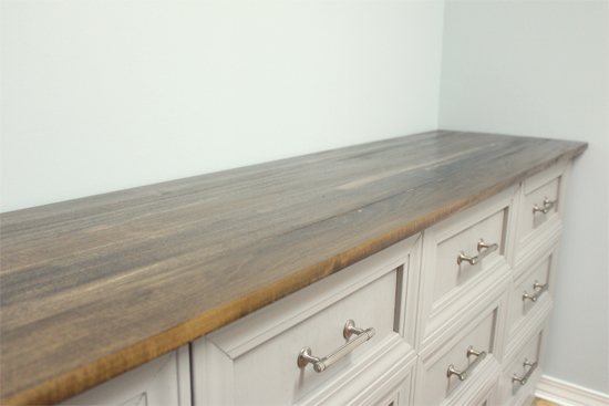stained wood countertop on gray dresser in blue laundry room