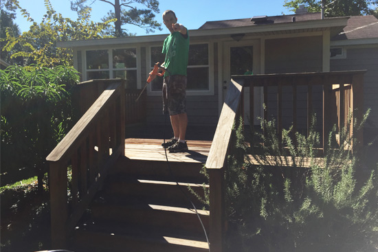 Male power washing wood deck with sun in background