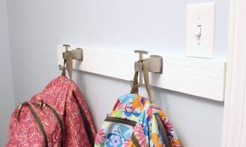 brushed nickel robe hooks backpack hanging system in organized laundry room