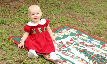 1 year old in Christmas dress posing for holiday card in grass on blanket
