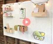 white painted pegboard hanging in garage with frame and custom bins hanging on pegs