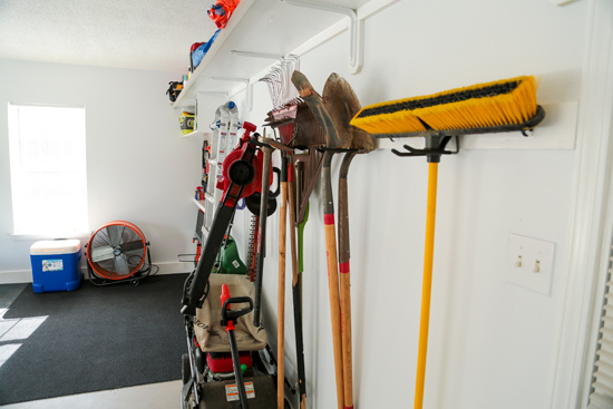 Lawn and Garden Tools Hanging on Back Wall in Garage