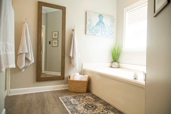 Bathtub and Shower Area of Master Bathroom with Gray Vinyl Plank Floors