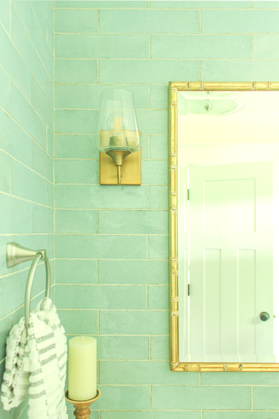 Gold Sconces and Gold Bamboo Mirror on Seafoam Blue Green Subway Tile Accent Wall