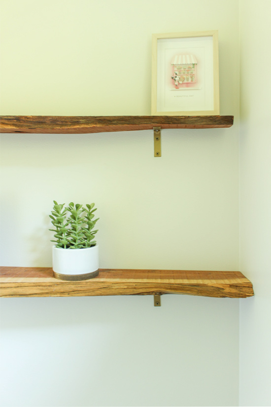 Two Sealed Wood Shelves with Gold Brackets Above Toilet