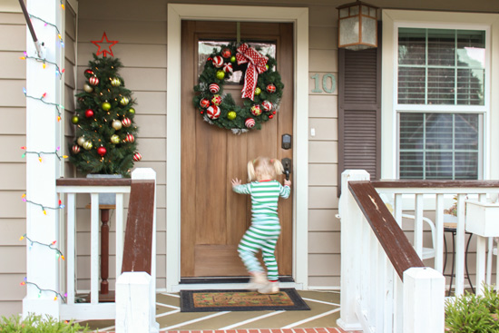 Toddler Girl Opening Wood Front Door at Christmas