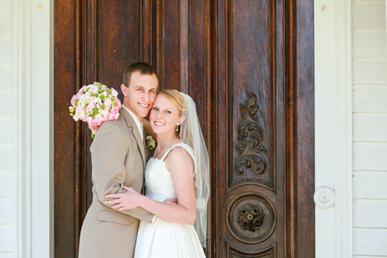 Happy Bride and Groom on Wedding Day in Front of Ornate Wood Doors