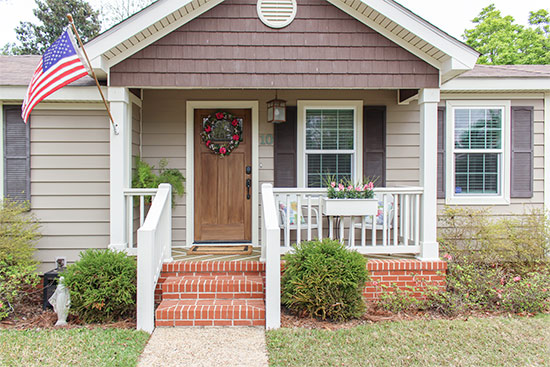 Tan Vinyl Siding House with Wood Front Door and White Handrails