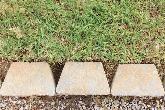 Green Grass Edged Behind Gray Pavestone Retaining Wall Blocks
