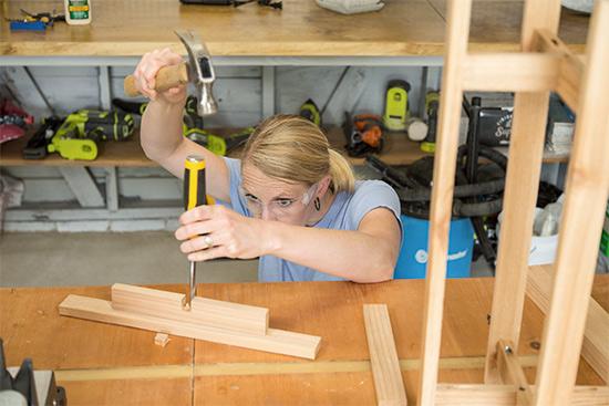 Chelsea Lipford Wolf using Dewalt wood chisel in workshop to build cedar wood planter stand