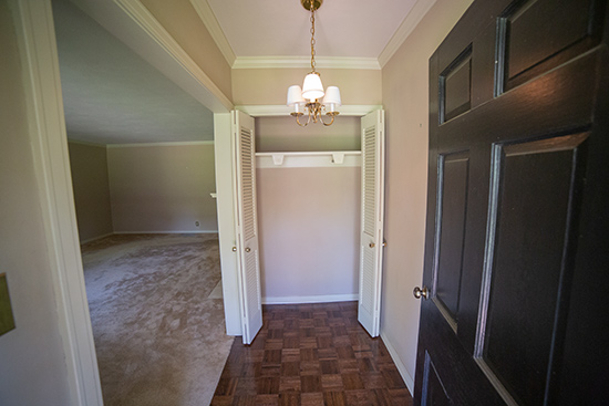 Front Foyer Entry with Parquet Wood Floors and Bi-Fold Doors Coat Closet