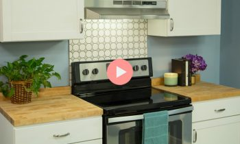 Butcher Block Countertop with Black and Stainless Stove in Blue Kitchen with White Cabinets