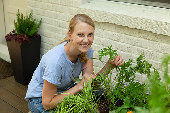 chelsea lipford wolf wearing periwinkle t-shirt smelling citronella plant on deck