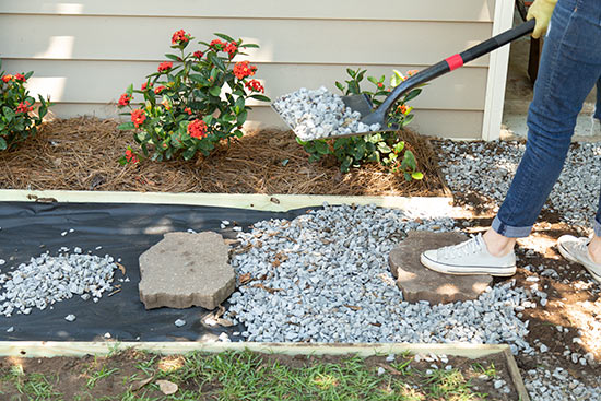 Shoveling Rocks from Driveway into New Pathway Walkway